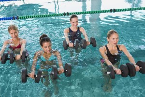 Female fitness class doing aqua aerobics with foam dumbbells in